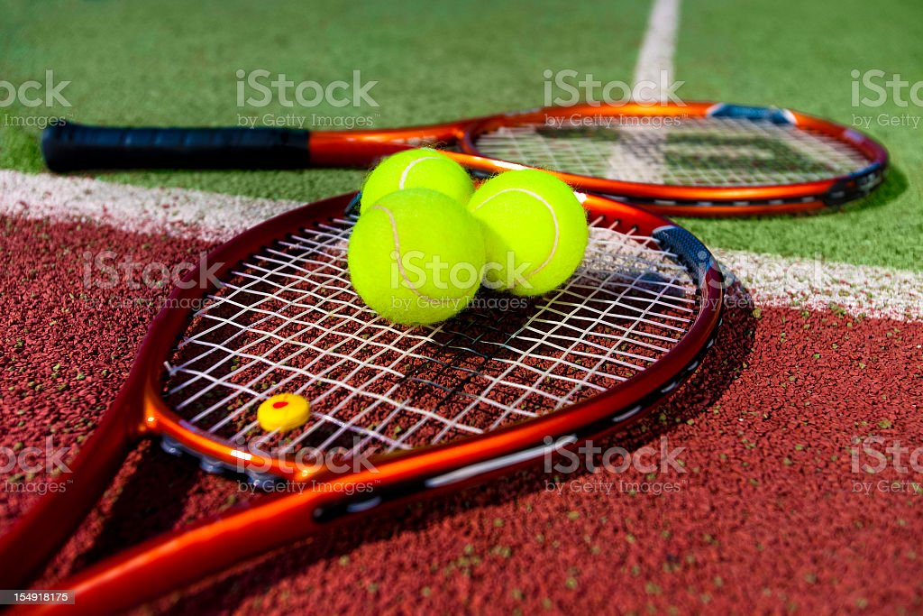 Two tennis rackets on court with three tennis balls on one royalty-free stock photo