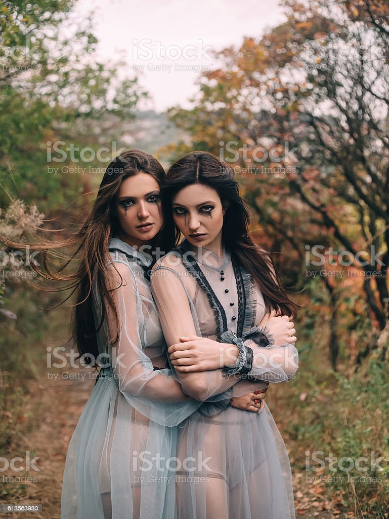 Two terrible lady in long white dresses, hugging each other stock photo