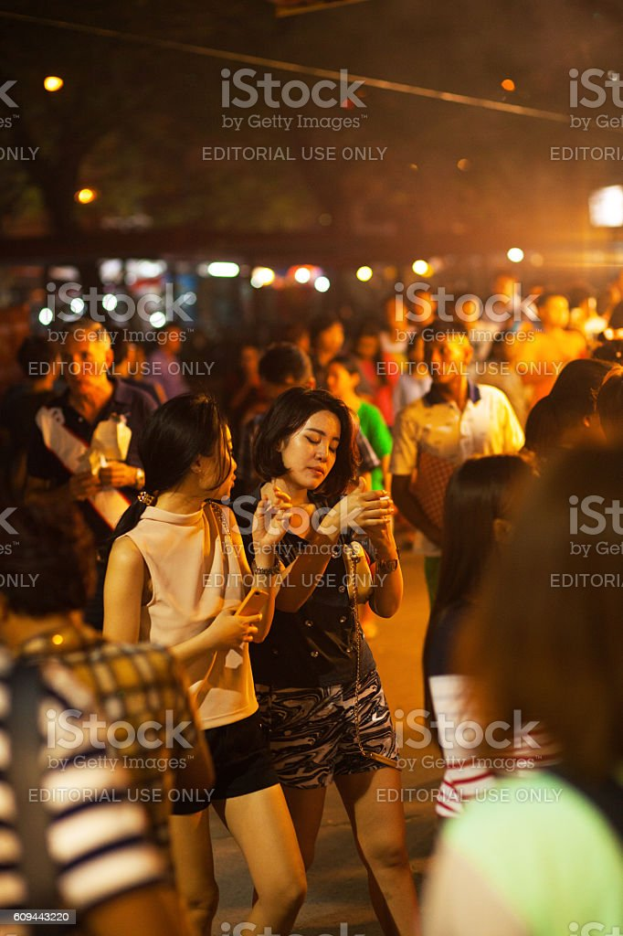 Two thai girls in crowd on night market stock photo