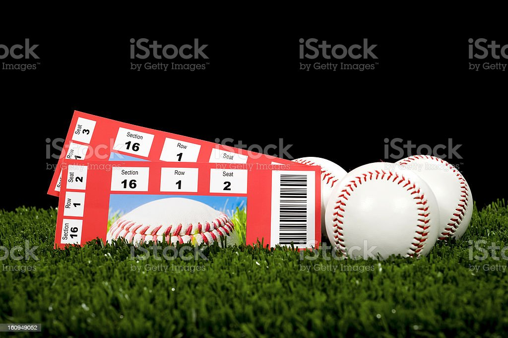 Two tickets of baseball games resting on grass with balls royalty-free stock photo