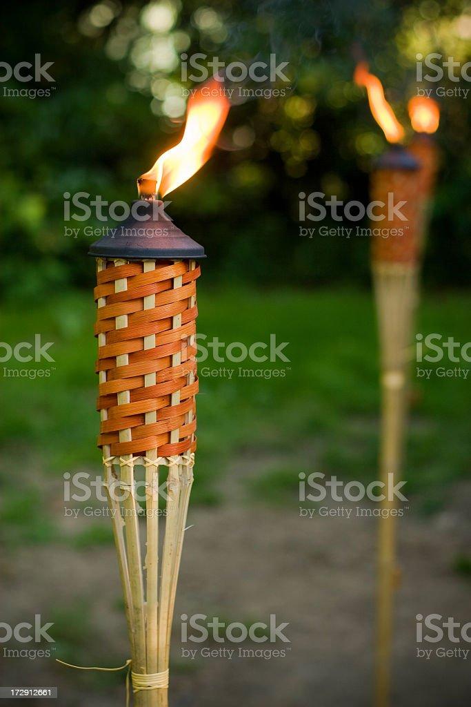 Two tiki torches burning outside stock photo