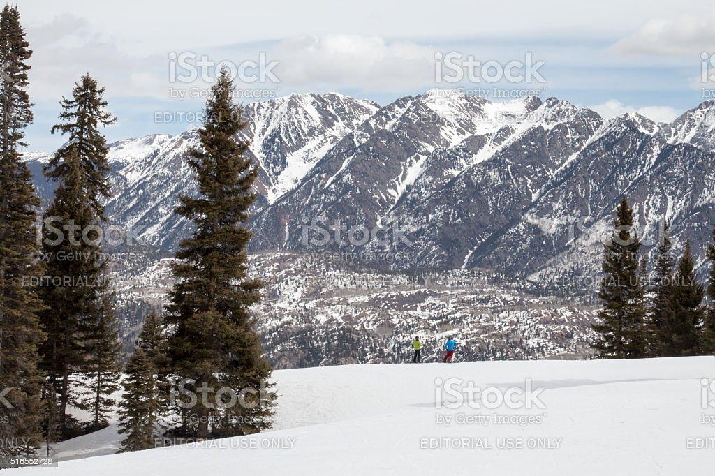 Two tiny skiers and majestic mountains - Purgatory resort stock photo