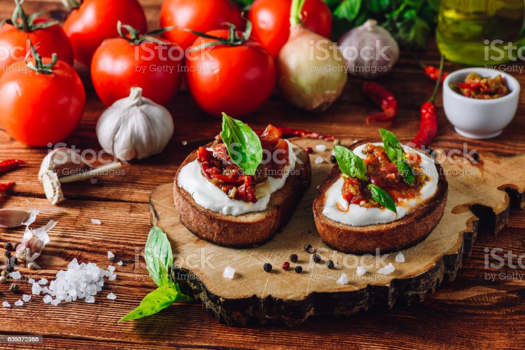 Two Toasts with Dried Tomatoes and Spicy Sauce stock photo