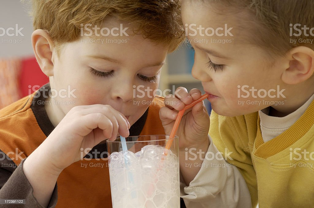 Two toddlers drinking milk in a glass with two straws royalty-free stock photo