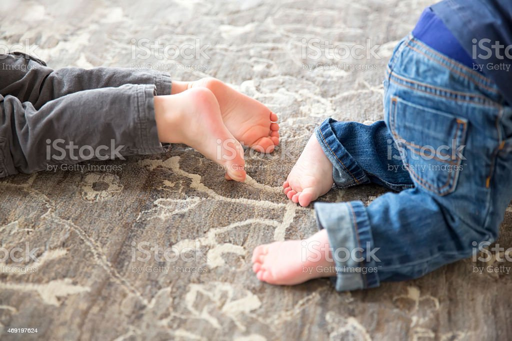 Two toddlers feet playing on the ground stock photo