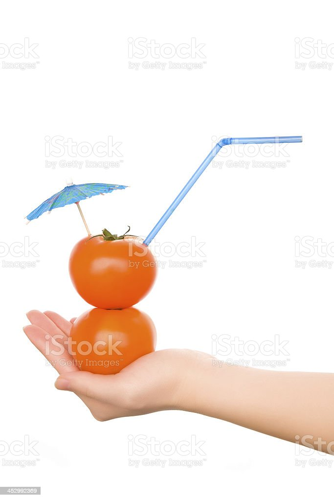 Two tomatos with straw and cocktail umbrella royalty-free stock photo