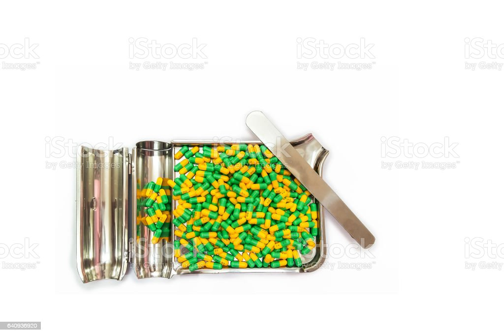 Two tone Medicine Capsules on Stainless Steel drug tray, Yellow Green Pills and Plate stock photo