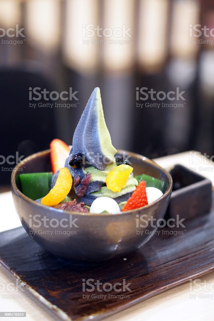 Two Tone soft served ice cream, green tea and charcoal served in black bowl decorated with fresh strawberry, orange, mochi balls and red bean. stock photo