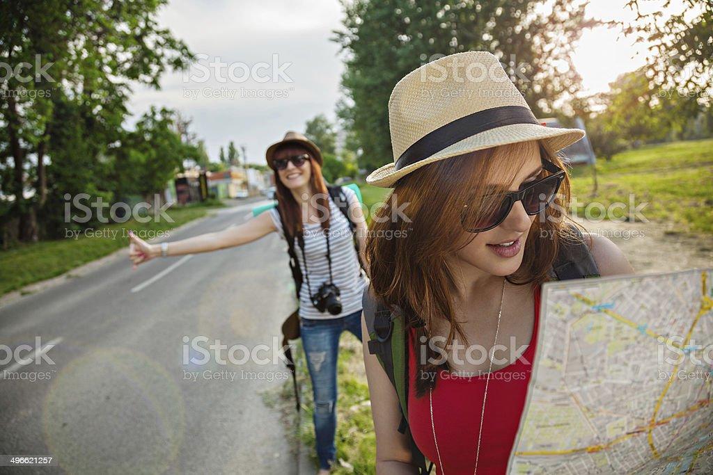 Two Tourist Girl Hitchhiking stock photo