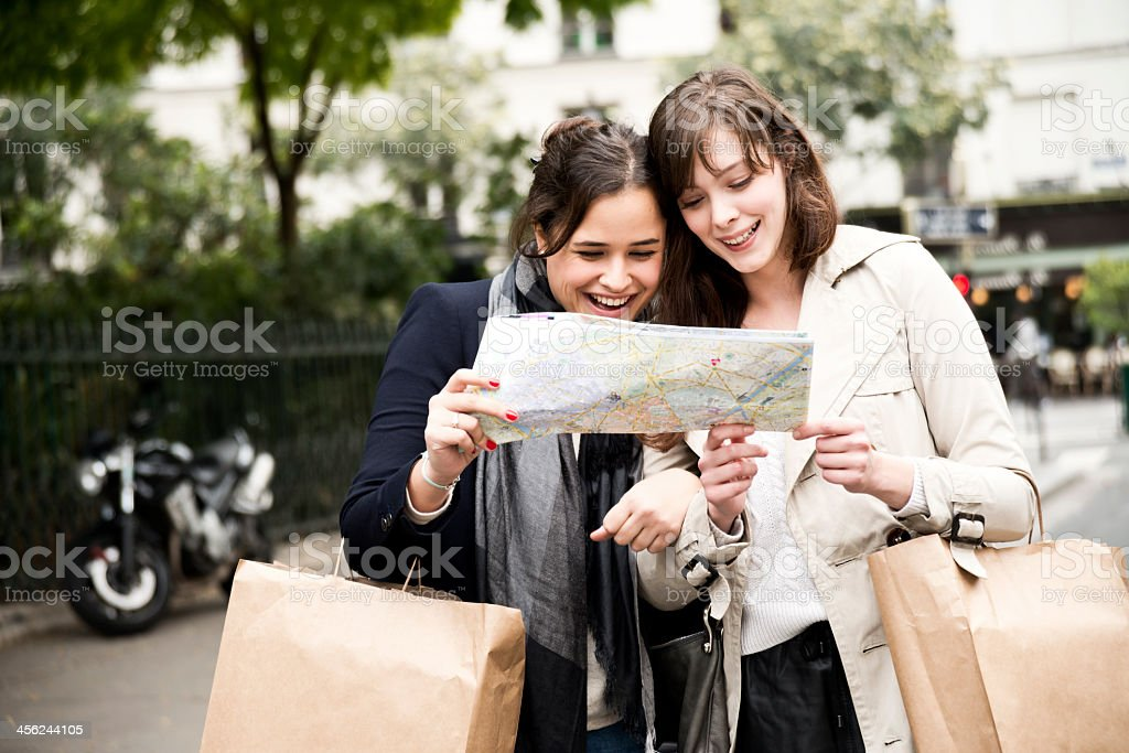 Two tourist girls looking at a map on streets in Paris stock photo