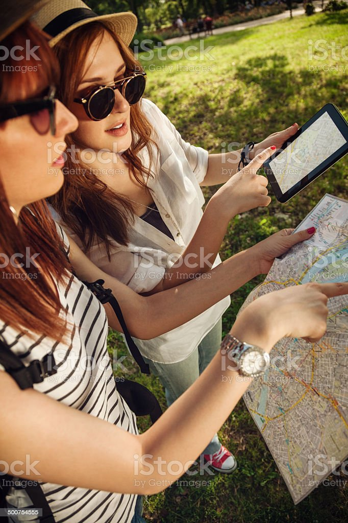Two Tourist Girls Using Map And Digital Tablet stock photo