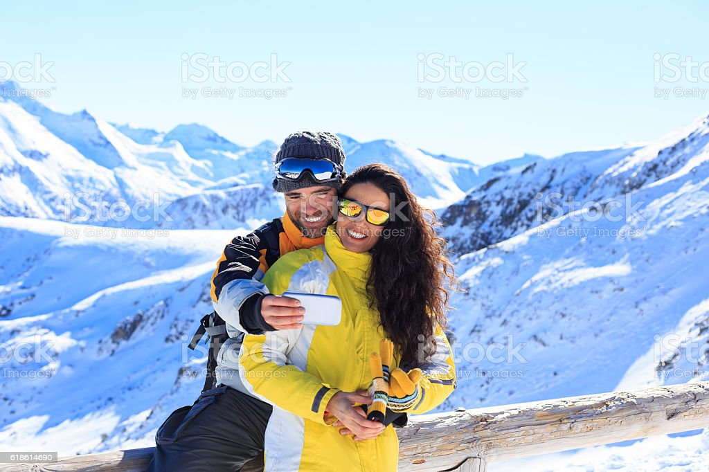 Two tourists making selfie on top mountain stock photo