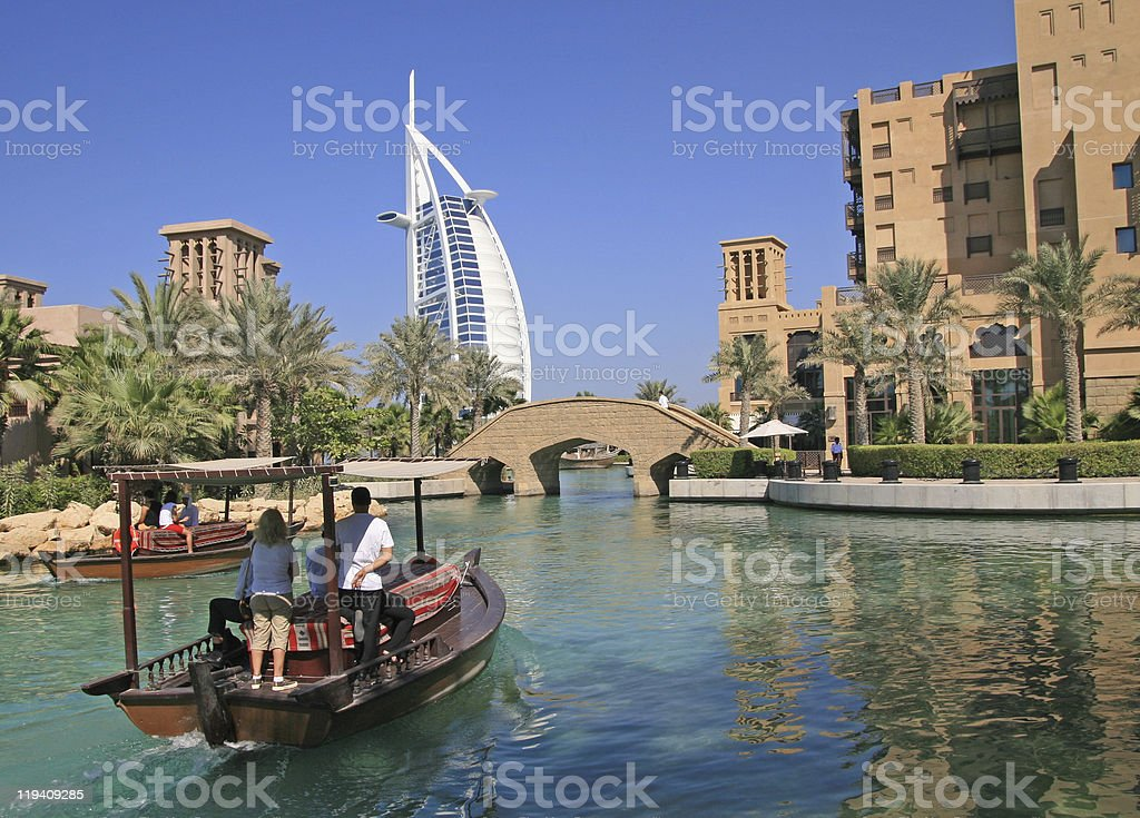 Two tourists taking a Boat Ride towards a luxurious Dubai hotel stock photo