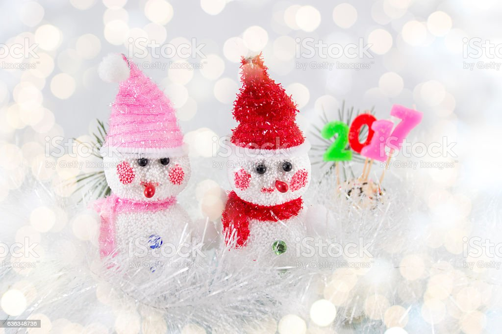 Two toy snowman with festive Christmas background stock photo