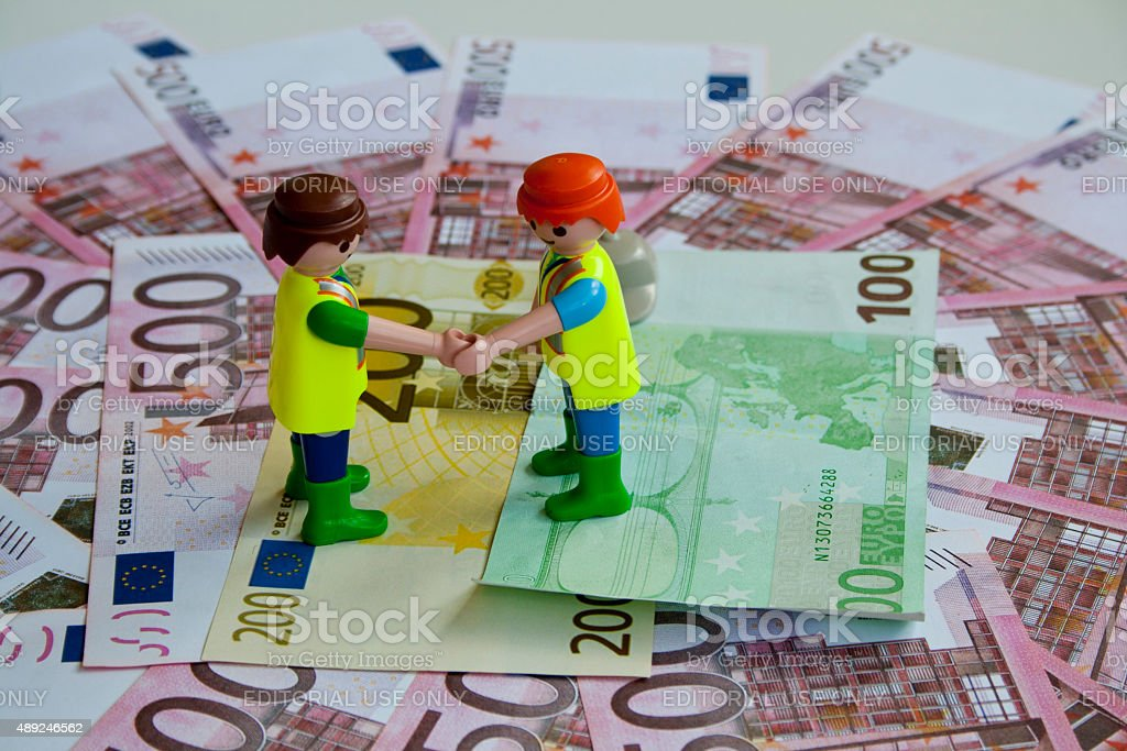 Two toy workers shake his hands to reach money agreement. stock photo