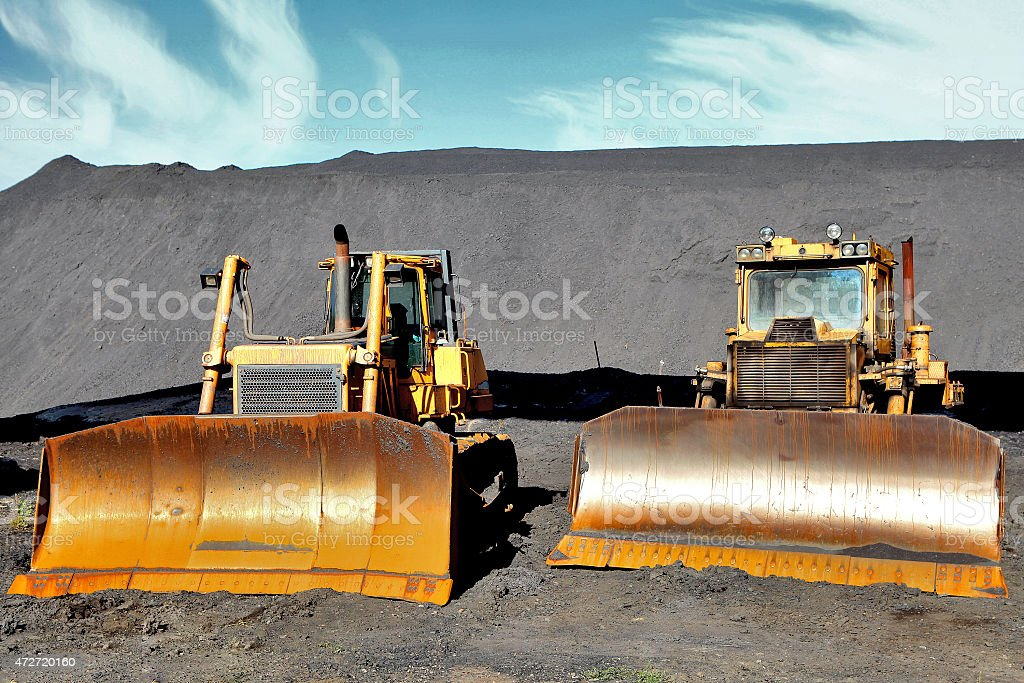 Two tractor on the background of the mountains of coal stock photo