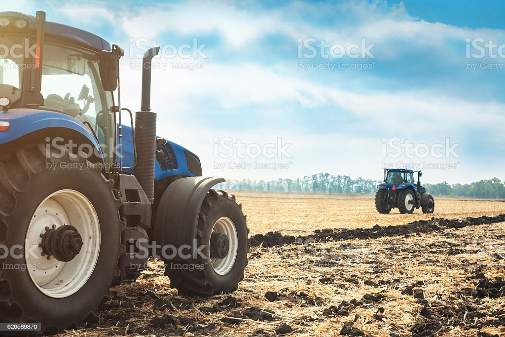 Two tractors working in a field. stock photo