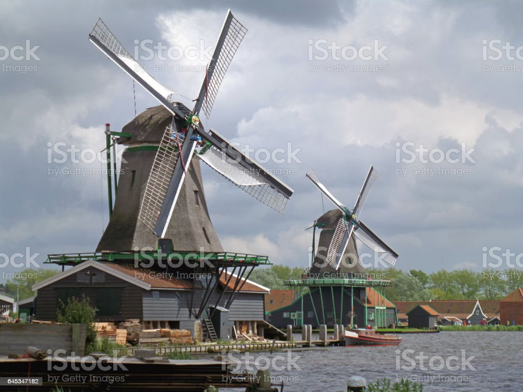 Two traditional Dutch windmills against Cloudy Sky stock photo