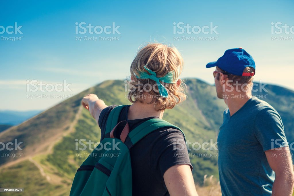 Two travelers discuss about itinerary on the top of mountain hill stock photo