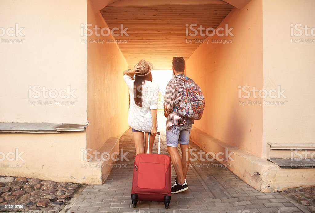 Two travelers on vacation walking around city with luggage stock photo