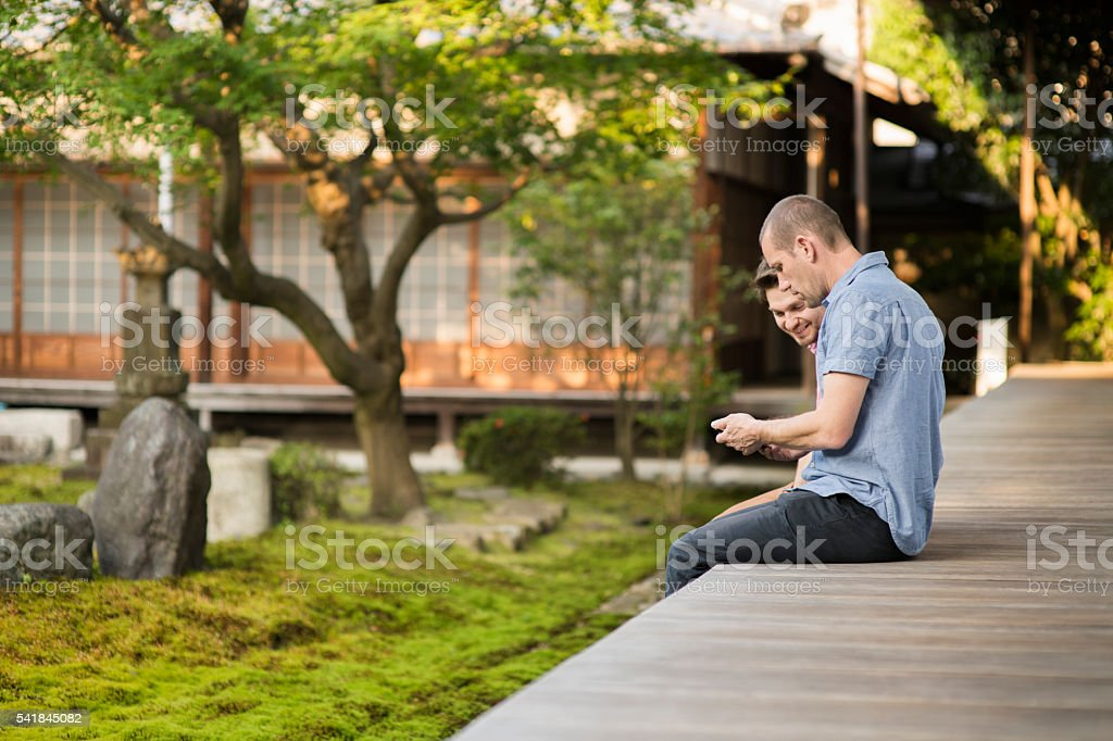 Two travelers watching smartphone in a Japanese temple stock photo