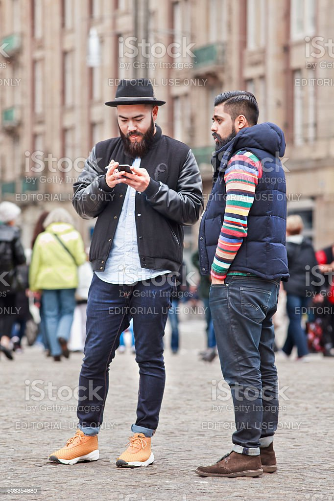 Two trendy Asian men with beard on Amsterdam Dam Square stock photo