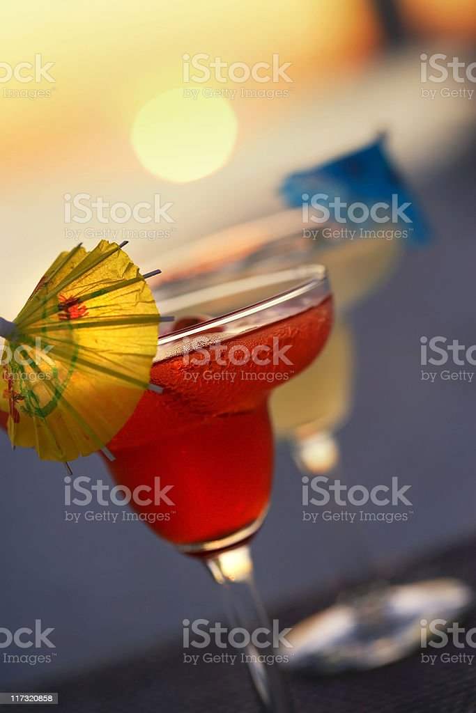 Two tropical cocktail drinks on the beach at sunset stock photo