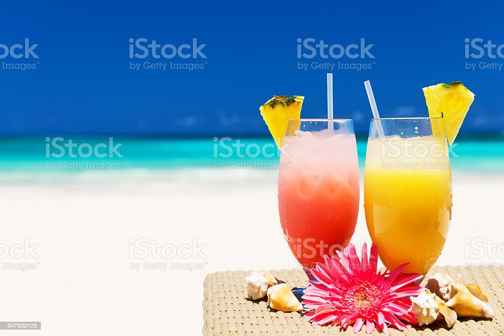 Two tropical fresh juices on white sandy beach stock photo