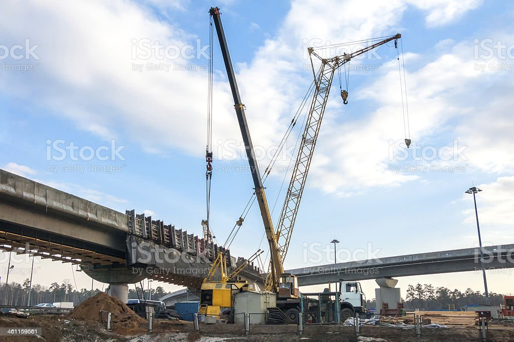 Two truck cranes stand with long crossed jibs before bridges stock photo