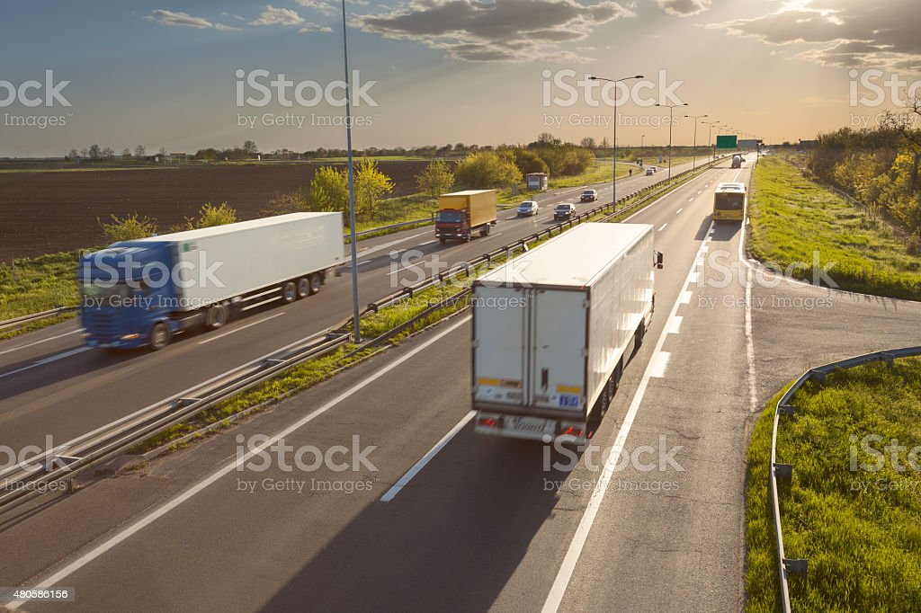 Two trucks on the highway at sunset in motion blur stock photo