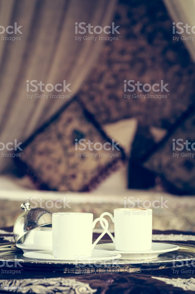 Two turkish coffee cups with oriental canopy bed at the background stock photo