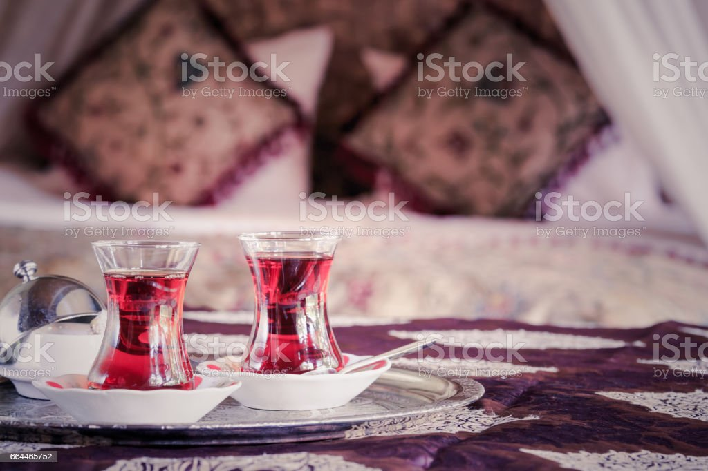 Two turkish tea cups and turkish delight with oriental canopy bed stock photo