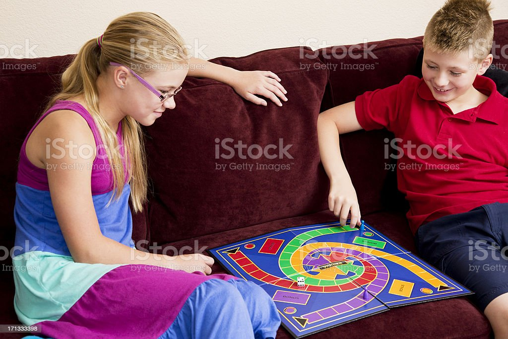 Two tweens playing board game in a living room stock photo