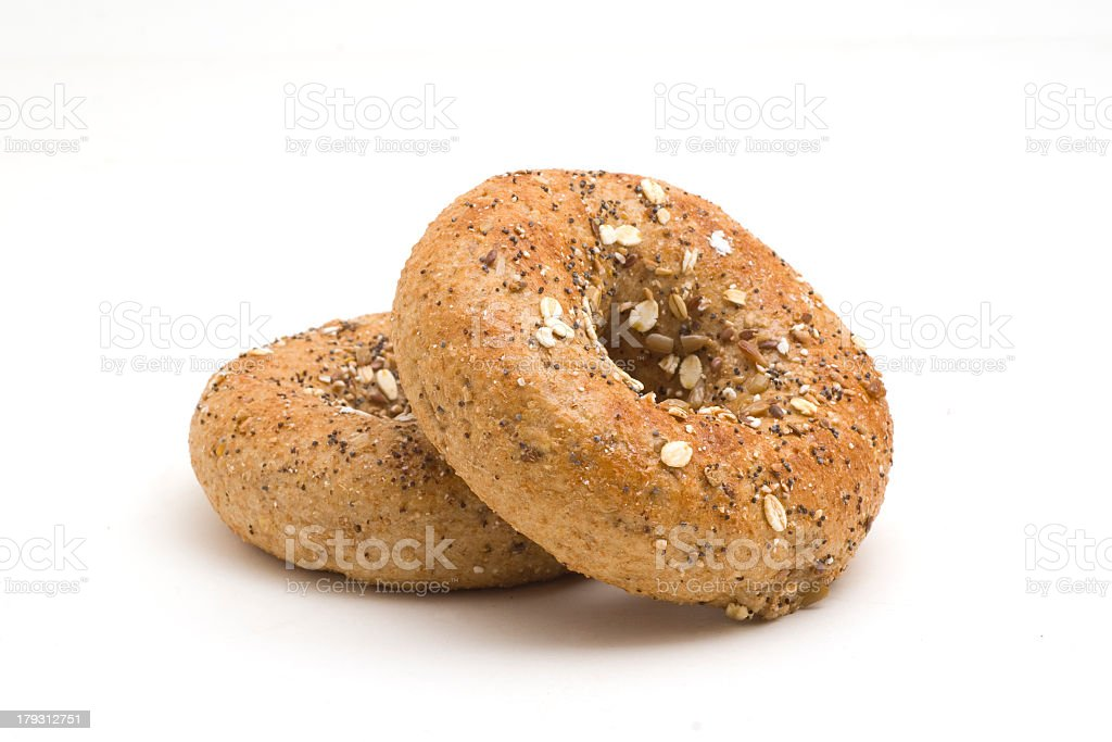 Two twelve grain bagels sitting on a white surface stock photo