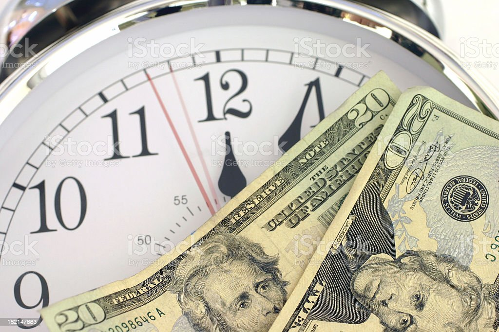 Two twenty dollar bills on top of a clock royalty-free stock photo