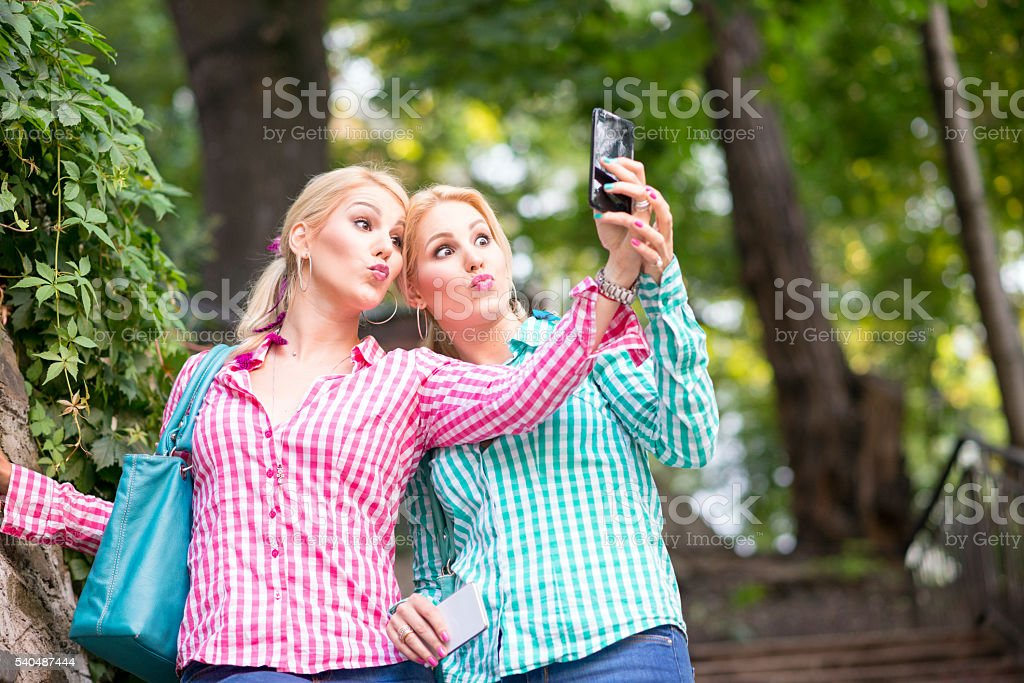 Two twin sisters making selfie with smart phone stock photo