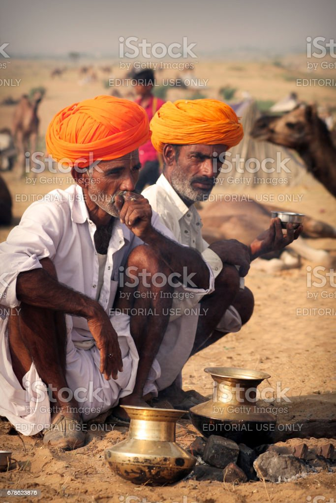 Two unidentified Indian Rajasthani men in their rural attire sitting on ground, one is smoking beedi and the other one is sipping some beverage at Pushkar Camel Fair stock photo