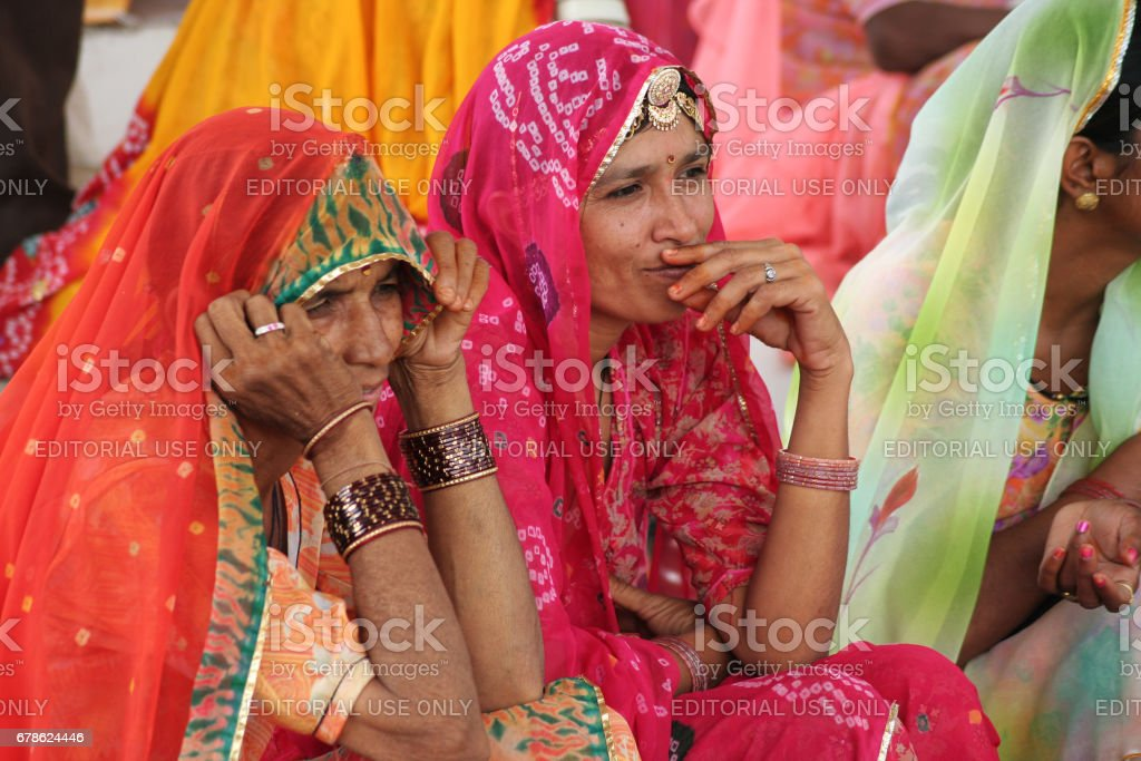 Two unidentified Indian Rajasthani women dressed in typical Rajasthani colorful and vibrant attire stock photo
