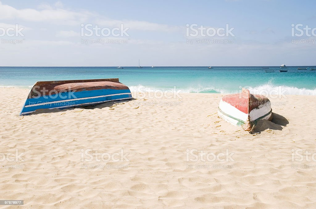 Two upturned boats on beach stock photo