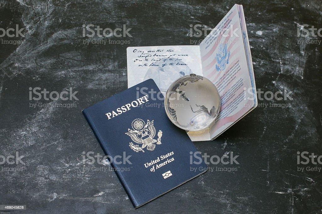 Two US passports and small glass globe on black background stock photo