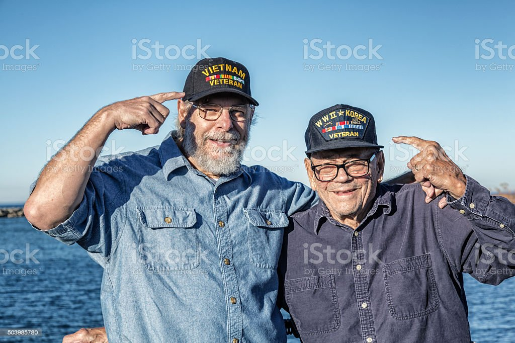 Two USA Military War Veterans Pointing At Souvenir Hats stock photo
