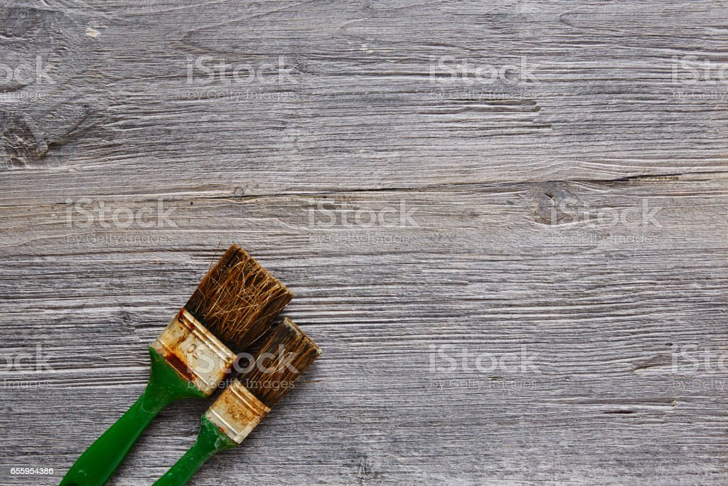 two used and rusty paintbrushes in workshop atmosphere stock photo