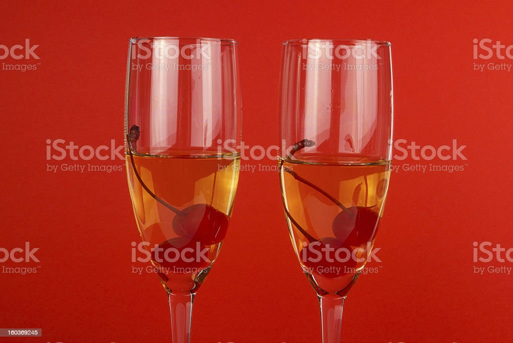 Two Valentine champagne glasses with cherry on red royalty-free stock photo