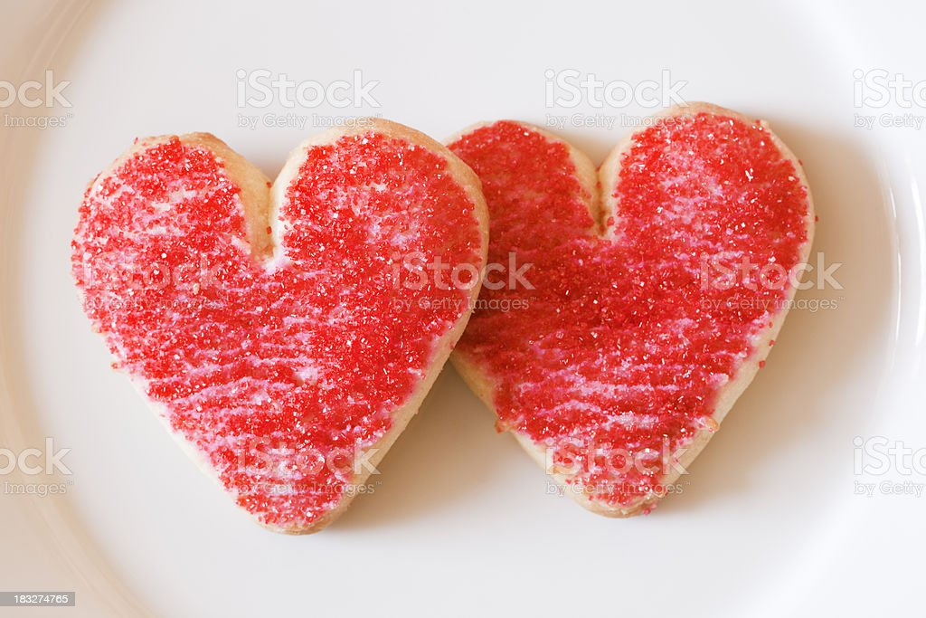 Two Valentine Red Heart Sugar Frosted Cookies on Plate Close-up stock photo