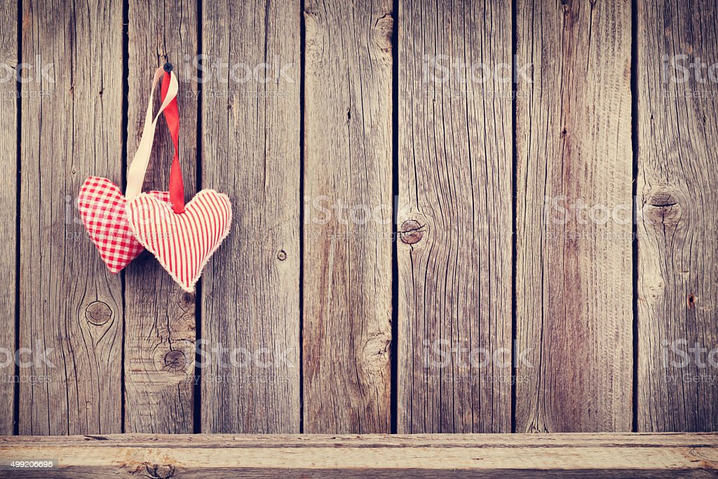 Two Valentines day hearts on rustic wooden wall stock photo