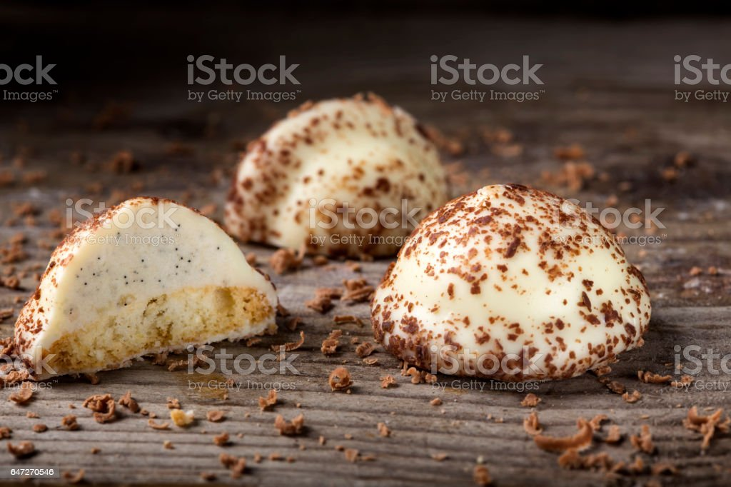 Two vanilla pearl candy, one cut in half, and grated dark chocolate on wood stock photo