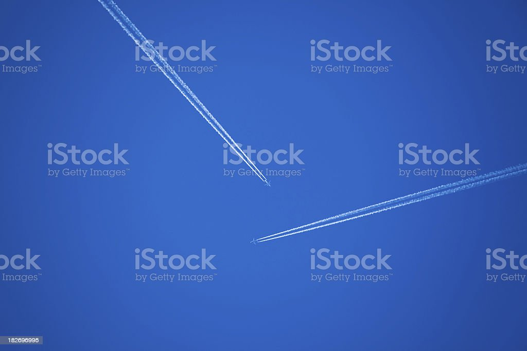 Two vapor trails with crossing trajectories royalty-free stock photo