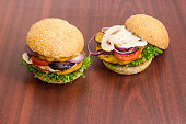 Two veggie burger with vegetables patties on a wooden surface