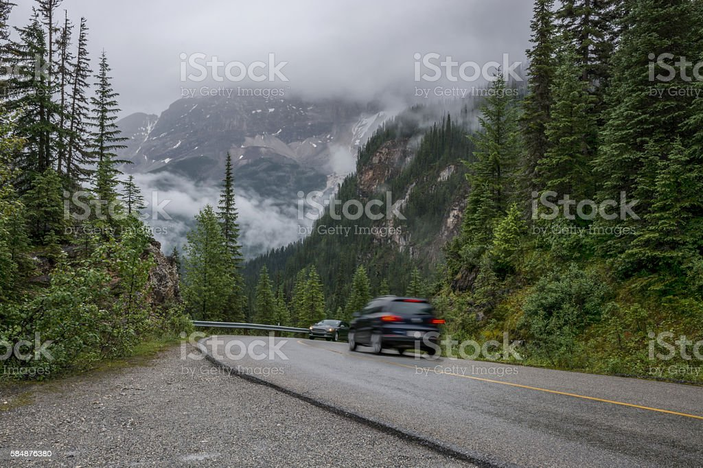 Two Vehicles Meet on a Hairpin Curve in a Mountain Road stock photo