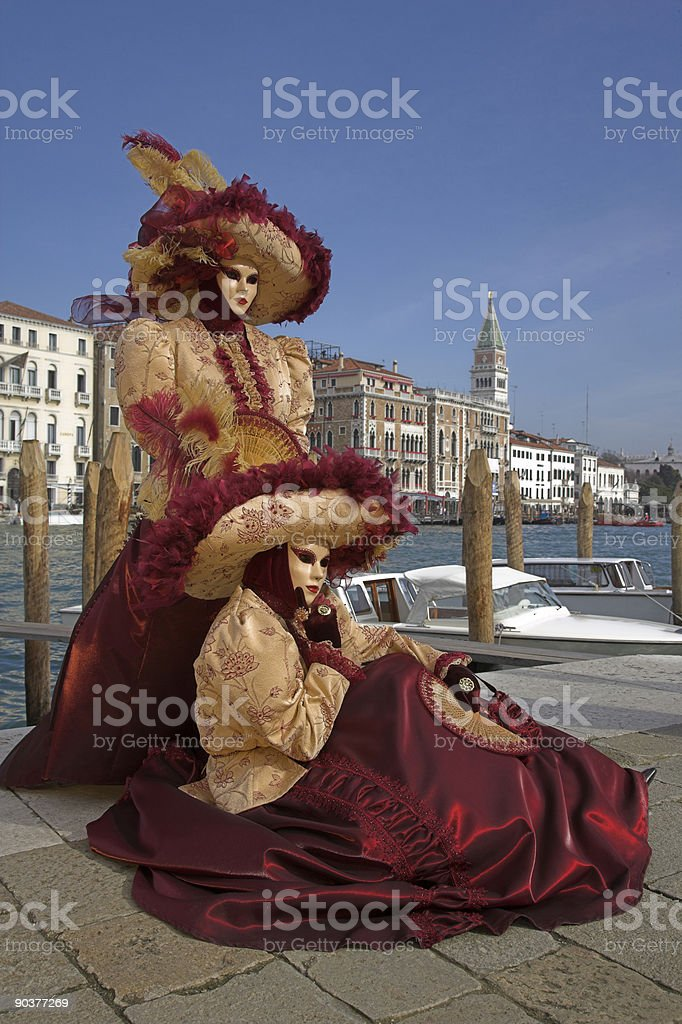 Two venetian masks in beautiful creative costumes at Grand Canal royalty-free stock photo